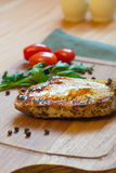 Juicy grilled pork chop (neck cut) on cutting board. Royalty Free Stock Image