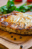 Juicy grilled pork chop (neck cut) on cutting board. Royalty Free Stock Photo