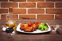 Juicy grilled pork fillet served with cherry tomatoes branch and lettuce on white plate. Background: brick wall. Close-up. Horizon. Tal Royalty Free Stock Photos