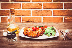 Juicy grilled pork fillet served with cherry tomatoes branch and lettuce on white plate. Background: brick wall. Close-up. Horizon. Tal Royalty Free Stock Images