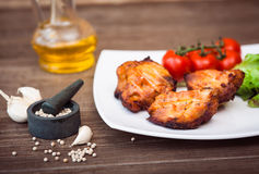 Juicy grilled pork fillet served with cherry tomatoes branch. And lettuce on white plate. Background: wooden boards. Close-up. Horizontal Stock Photo