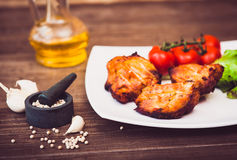 Juicy grilled pork fillet served with cherry tomatoes branch. And lettuce on white plate. Background: wooden boards. Close-up. Horizontal Stock Photos