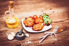 Juicy grilled pork fillet served with cherry tomatoes branch and lettuce on white plate. Background: wooden boards. Close-up. Hori. Zontal Stock Photography