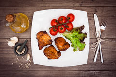 Juicy grilled pork fillet served vegetables and spices. Juicy grilled pork fillet served with cherry tomatoes branch and lettuce on white plate, white pepper Royalty Free Stock Photography
