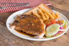 Juicy grilled pork with garlic sauce and salad, french fries. Juicy grilled pork with garlic sauce and salad, french fries Stock Image