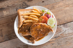 Juicy grilled pork with garlic sauce and salad, french fries. To Royalty Free Stock Photos