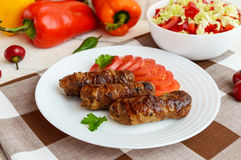 Juicy grilled rolls of minced meat wrapped in bacon with fresh tomato and a light salad of Chinese cabbage Stock Images