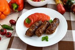 Juicy grilled rolls of minced meat wrapped in bacon Stock Photo