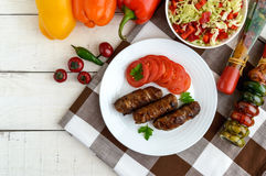 Juicy grilled rolls of minced meat wrapped in bacon with fresh tomato and a light salad of Chinese cabbage Stock Photography