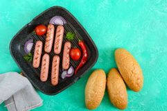 Juicy grilled sausages on grill pan with vegetables and crispy bun. Stock Image