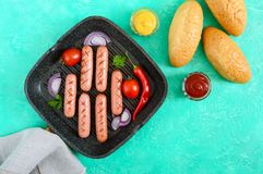 Juicy grilled sausages on grill pan with vegetables and crispy bun. Top view. Stock Photo