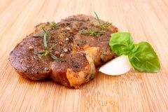 Juicy grilled steak on bamboo board with basil and onion Stock Images