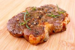 Juicy grilled steak meat with herb marinade on bamboo board Royalty Free Stock Photography