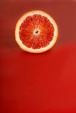 Juicy half of a blood orange on a red background Stock Photography