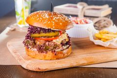 Juicy hamburger with beef burger cutlet, onion, lettuce, pickles, tomatos and cheese sauce in traditional buns, served on wood royalty free stock photos