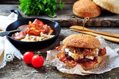 Juicy homemade double burger beef with fried onions on a wooden background Stock Photography