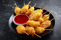 Juicy king prawns wrapped in little spirals of crisp, golden potato on skewers served with sweet chillie sauce. Juicy king prawns wrapped in little spirals of Stock Photography