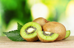 Juicy kiwi fruit on wooden table on green Stock Images