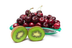 Juicy kiwi and ripe cherry closeup on a white background Royalty Free Stock Photo
