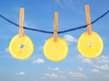 Juicy lemon hanging on the rope on sky background Stock Images