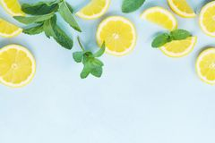 Juicy lemon slices and mint leaves on blue table top view. Flat lay style. Juicy lemon slices and mint leaves on blue table top view. Flat lay Royalty Free Stock Photography