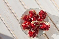 Juicy lobules of garnet on plate Stock Image