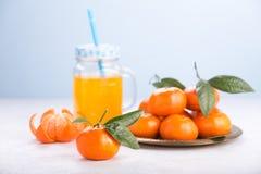 Juicy mandarins with green leaves. Fresh tangerines on a white table. Juicy mandarins with green leaves. Glass mug with handle orange background clementine fruit stock photo