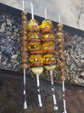Juicy marinated in spices meat kebab on skewers, cooked and fried on a fire and charcoal barbecue grill, in the nature of snowy royalty free stock image