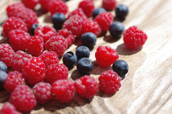 Juicy mature berries of raspberry and bilberry Royalty Free Stock Image