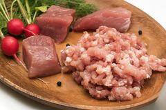 Juicy meat chopped in minced close-up served with large pieces of raw meat fresh vegetables, seasoning and herbs. Kitchen, food, products, ingredients, meat royalty free stock image