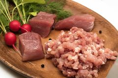 Juicy meat chopped in minced close-up served with large pieces of raw meat fresh vegetables, seasoning and herbs. Kitchen, food, products, ingredients, meat stock photo