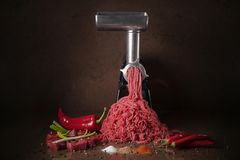 Juicy meat climbs out of the meat grinder. stock image