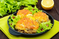 Juicy meat cutlet, baked with grated potatoes and cheese on a cast-iron frying pan on a dark wooden background. Royalty Free Stock Images