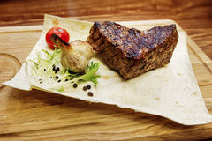Juicy meat grilled steak with red pepper tomato and garlic. serv. Ing beefsteak on wooden desk. catering in food court at mall concept. space for text. modern Stock Images
