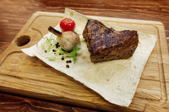 Juicy meat grilled steak with red pepper tomato and garlic. serv. Ing beefsteak on wooden desk. catering in food court at mall concept. space for text. modern Royalty Free Stock Images
