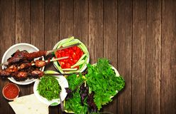 Meat kebab of lamb and beef with fresh herbs appetizing lie on a wooden table royalty free stock photo