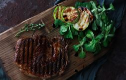 The juicy meat steak grilled with zucchini, spinach on wooden board Stock Photo