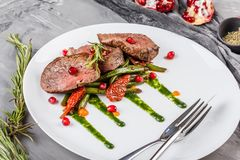 Juicy medium beef fillet steaks mignon with green beans, pomegranate and sauce in plate on grey background. Hot Meat Dishes. Top view stock photography