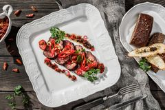 Juicy medium beef fillet steaks mignon with pepper, spices in plate on rustic wooden background. Hot Meat Dishes. Top view royalty free stock images