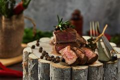 Juicy medium pieces of rib eye beef steak in a pan on a wooden board with a fork and knife. Spices and herbs, background, barbecue, bbq, beefsteak, closeup stock image