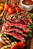 Juicy medium rare sliced grilled fillet steak served with tomato Stock Image