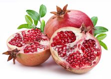 Juicy opened pomegranate with leaves. Royalty Free Stock Photo