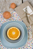 Juicy orange on blue plate is the old pad and tangles Royalty Free Stock Image