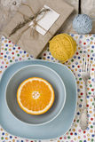 Juicy orange on blue plate is the old pad and tangles Royalty Free Stock Images