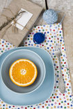 Juicy orange on blue plate is the old pad and tangles of yarn Stock Photos
