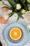Juicy orange on blue plate is the old pad and tangles of yarn Royalty Free Stock Photos