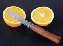 Juicy Orange and Folding Knife. Closeup view of two halves juicy orange and vintage folding knife with wooden handle against dark background Stock Photography