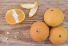 The juicy orange fruit was cut off, saw the fruit pulp on a wooden table. royalty free stock images