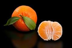 Juicy orange mandarin and half peeled mandarin on pure black background. Royalty Free Stock Photography
