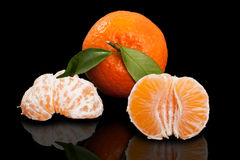 Juicy orange mandarin and two half peeled mandarin on pure black background. Royalty Free Stock Images